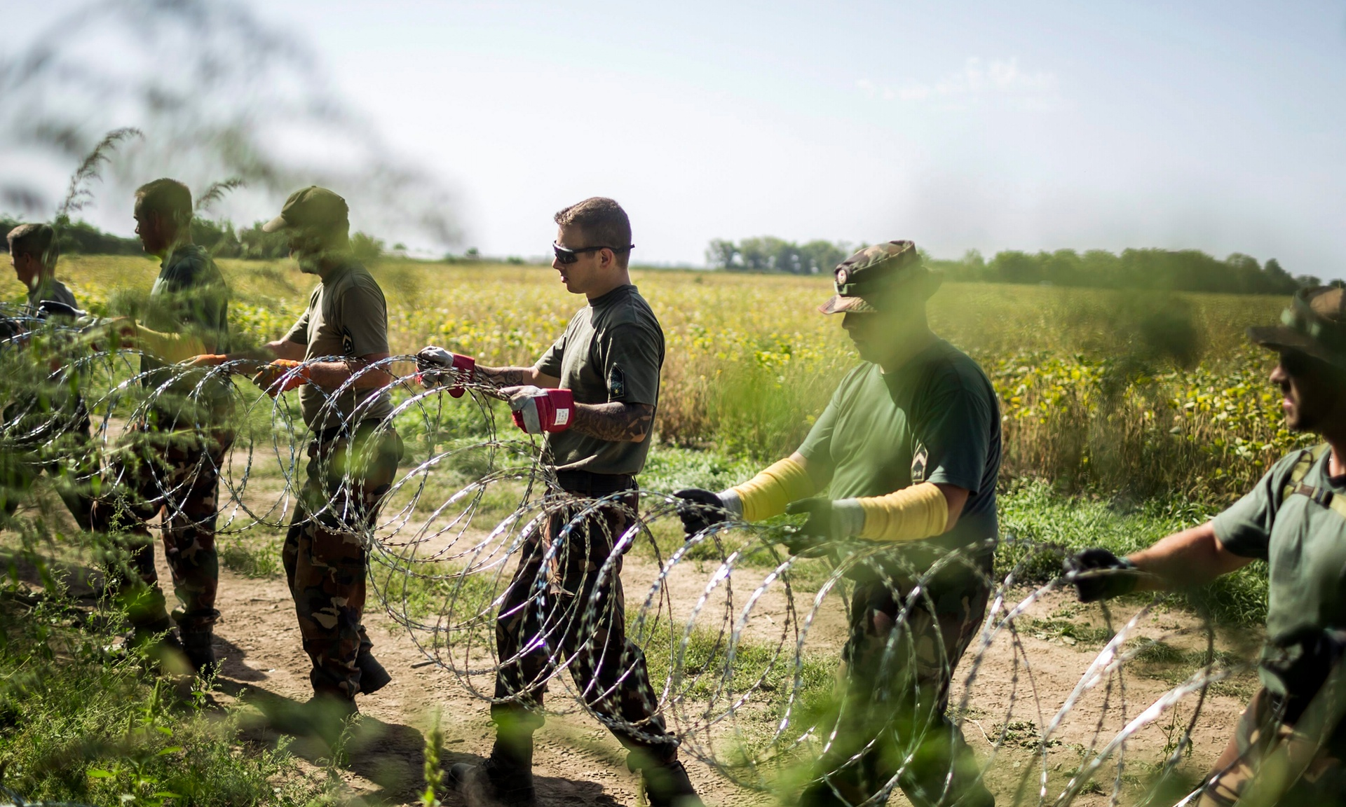 Soldiers set up a razor-wire fence to keep out refugees, on Hungary's southern border with Croatia. Photograph: Balazs Mohai/EPA